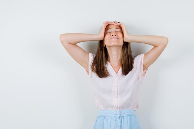 Jonge vrouw hand in hand op gezicht in t-shirt, rok en op zoek geïrriteerd, vooraanzicht.