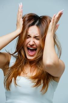 Jonge vrouw hand in hand op haar hoofd terwijl ze schreeuwt
