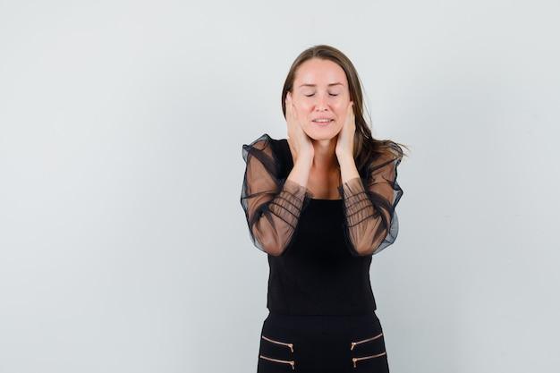 Jonge vrouw hand in hand op haar oren terwijl ze ogen in zwarte blouse sluit en kalm kijkt. vooraanzicht. ruimte voor tekst