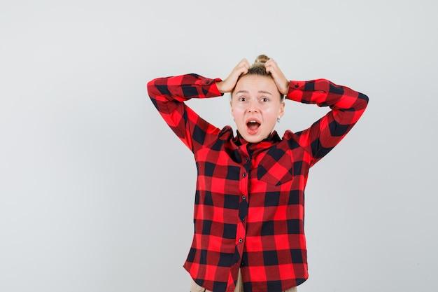 Jonge vrouw hand in hand op het hoofd in geruit overhemd, broek en vergeetachtig op zoek