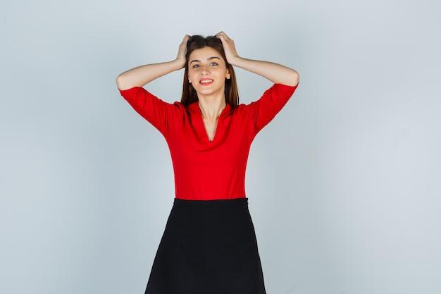 Jonge vrouw hand in hand op het hoofd in rode blouse, zwarte rok en op zoek vrolijk