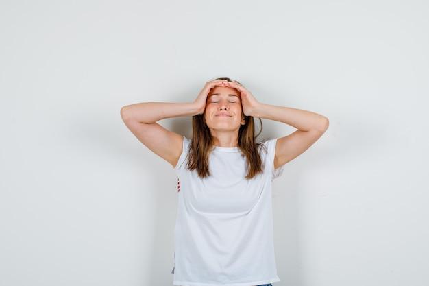Jonge vrouw hand in hand op het hoofd in wit t-shirt, korte broek en op zoek ontspannen. vooraanzicht.