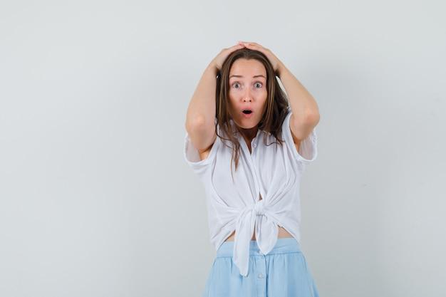 Jonge vrouw hand in hand op het hoofd in witte blouse en lichtblauwe rok en verbaasd kijken