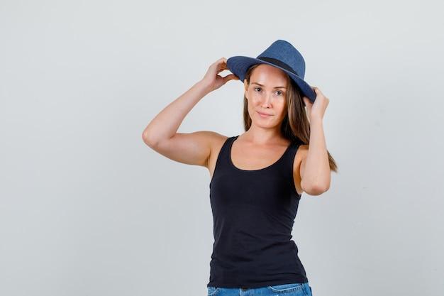 Jonge vrouw hand in hand op hoed en lachend in hemd, korte broek vooraanzicht.