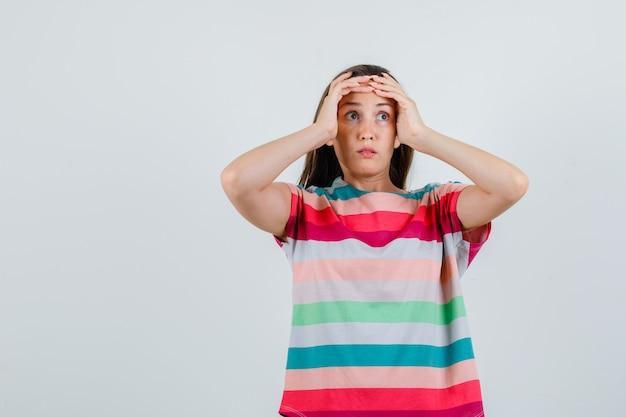 Jonge vrouw hand in hand op hoofd in t-shirt en op zoek verbaasd, vooraanzicht.
