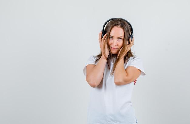 Jonge vrouw hand in hand op koptelefoon en lachend in wit t-shirt vooraanzicht.