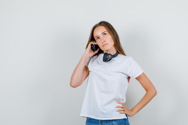 Jonge vrouw hand in hand op koptelefoon en taille in wit t-shirt, korte broek en peinzend op zoek