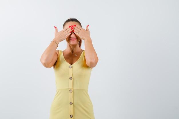 Jonge vrouw hand in hand op ogen in gele jurk en op zoek beschaamd, vooraanzicht.
