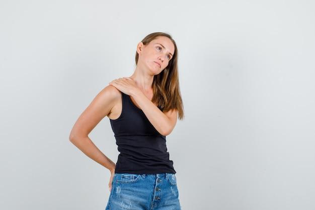 Jonge vrouw hand in hand op schouder en rug in hemd, korte broek en op zoek triest