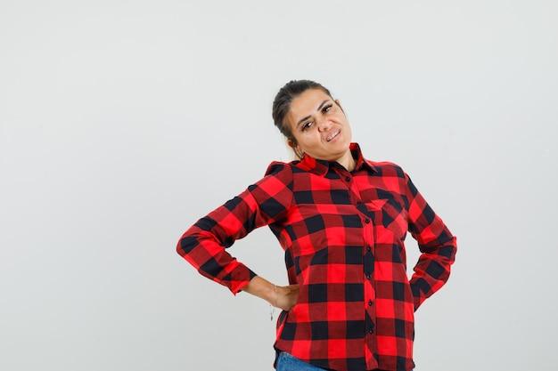 Jonge vrouw hand in hand op taille in geruit overhemd, korte broek en op zoek zelfverzekerd. vooraanzicht.