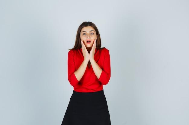 Jonge vrouw hand in hand op wangen in rode blouse, zwarte rok en verbaasd kijken