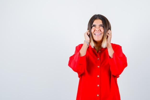 Jonge vrouw hand in hand op wangen in rood oversized shirt en ziet er vrolijk uit. vooraanzicht.