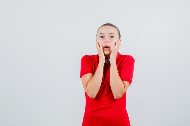 Jonge vrouw hand in hand op wangen in rood t-shirt en bang op zoek