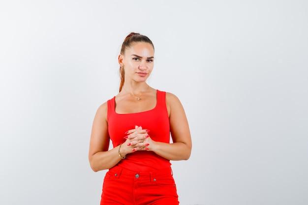 Jonge vrouw hand in hand voor zichzelf in rood mouwloos onderhemd, broek en op zoek verbaasd, vooraanzicht.