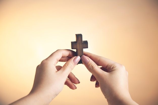 Jonge vrouw hand met houten kruis