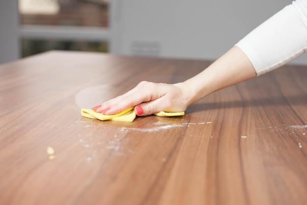 Jonge vrouw hand moderne houten tafel schoonmaken door stofdoek