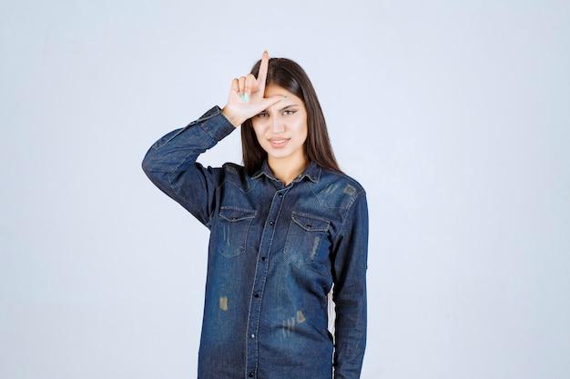 Jonge vrouw hand op haar voorhoofd zetten en verliezer teken tonen