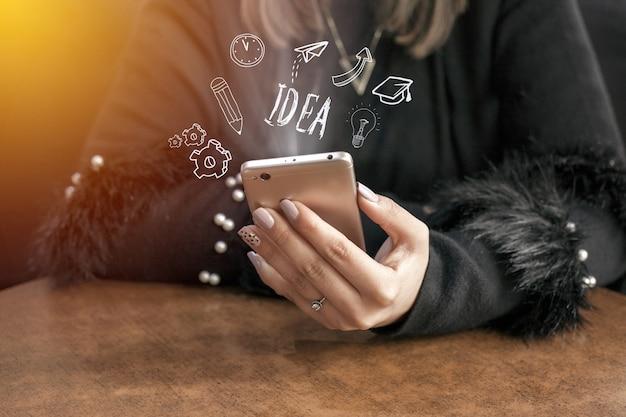 Jonge vrouw handen met behulp van smartphone met doodle zakelijke pictogrammen. communicatie concept.