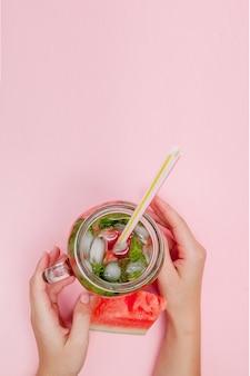 Jonge vrouw handen met vers geperste watermeloen limonade van citrusvruchten