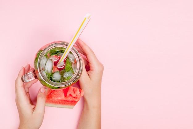 Jonge vrouw handen met vers geperste watermeloen limonade van citrusvruchten.