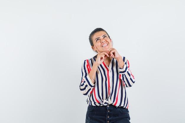 Jonge vrouw handen onder de kin zetten en iets in gestreepte blouse nadenken en optimistisch kijken