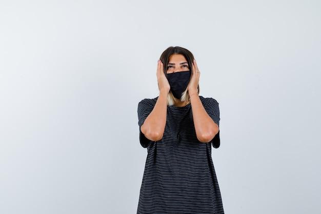 Jonge vrouw handen op de oren te drukken, naar boven kijkend in zwarte jurk, zwart masker en op zoek gekweld. vooraanzicht.