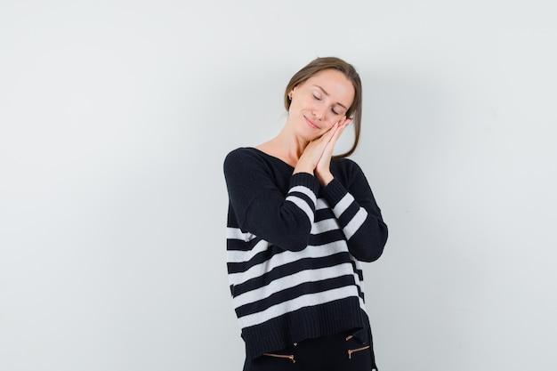 Jonge vrouw handen op de wang leunend en probeert te slapen in gestreepte gebreide kleding en zwarte broek en op zoek ontspannen