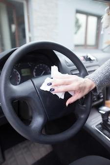 Jonge vrouw handen stof van haar auto schoonmaken met een doek