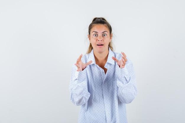 Jonge vrouw handen uitrekken als iets in een wit overhemd vasthouden en verbaasd kijken