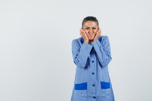 Jonge vrouw handen zetten in de buurt van de mond, wangen puffend in het blauwe overhemd van de ginghampyjama en op zoek nieuwsgierig, vooraanzicht.
