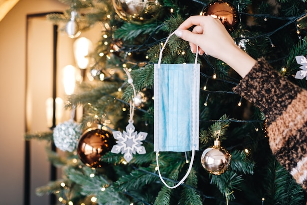 Jonge vrouw hangt een medisch beschermend masker aan de kerstboom