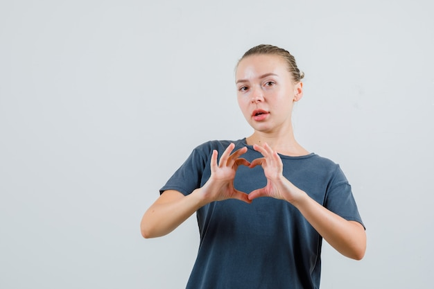 Jonge vrouw hart gebaar in grijs t-shirt tonen