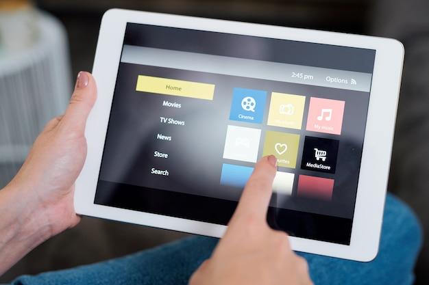 Jonge vrouw hartpictogram op touchpad-display aan te raken tijdens het kiezen van iets om naar te kijken
