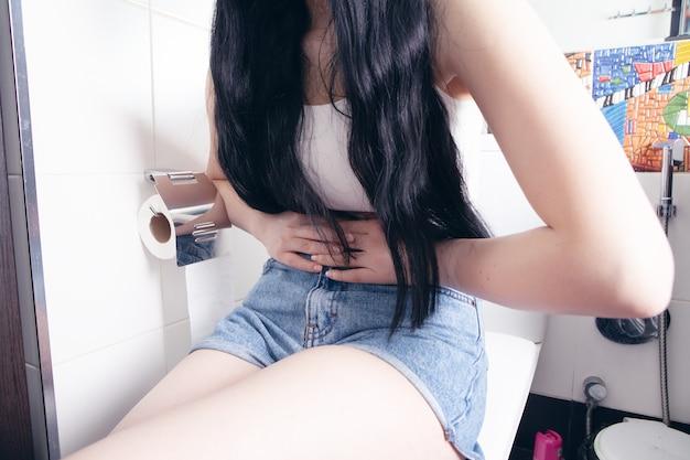 Jonge vrouw heeft buikpijn in toilet