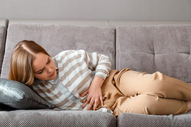 Jonge vrouw heeft buikpijn liggend op de bank in werkdag op kantoor. acute pijn bij een opgeblazen gevoel pms. tienermeisje met pijn problemen darmziekte.