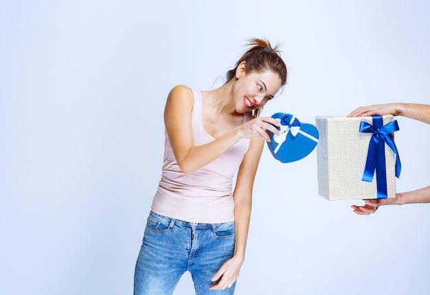 Jonge vrouw heeft een blauwe geschenkdoos in de vorm van een hart en krijgt nog een witte geschenkdoos aangeboden