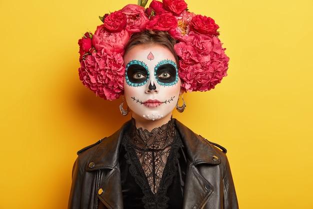 Jonge vrouw heeft funky make-up en kostuum, draagt krans van rode bloemen, heeft traditionele vooruitzichten voor tweedaagse mexicaanse vakantie, geïsoleerd op geel