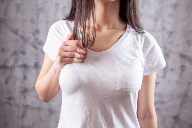Jonge vrouw heeft pijn op de borst op grijs