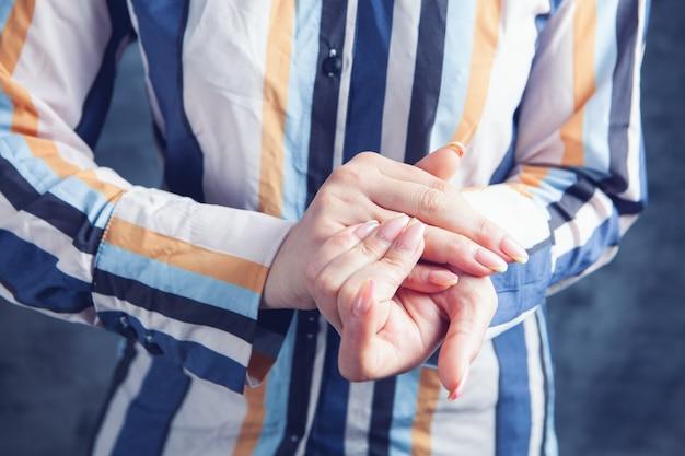 Jonge vrouw heeft pijnlijke vingers