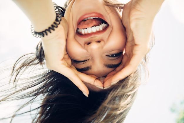 Jonge vrouw heeft plezier en wordt gek. close-upportret vanuit een ongebruikelijke invalshoek.
