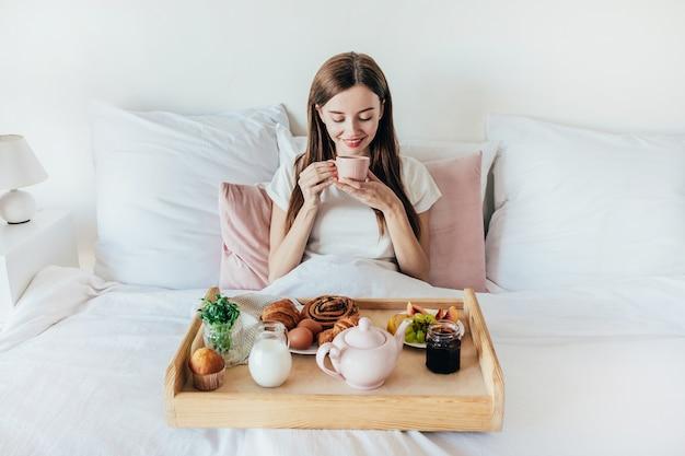 Jonge vrouw heeft 's ochtends ontbijt op bed