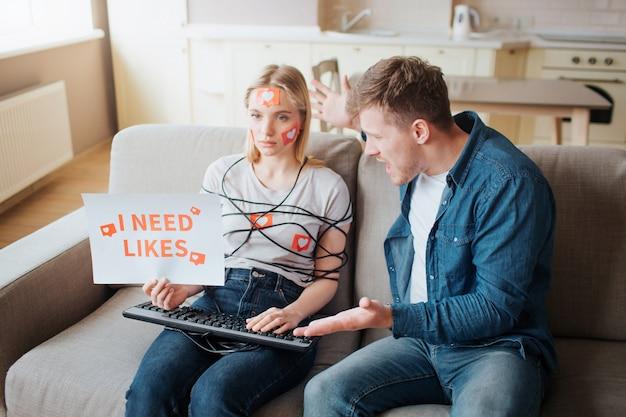 Jonge vrouw heeft sociale media verslaving. zorgeloos op de bank zitten. lichaam omwikkeld met koord. handen op toetsenbord. boze jonge man schreeuwen. emotionele mensen.