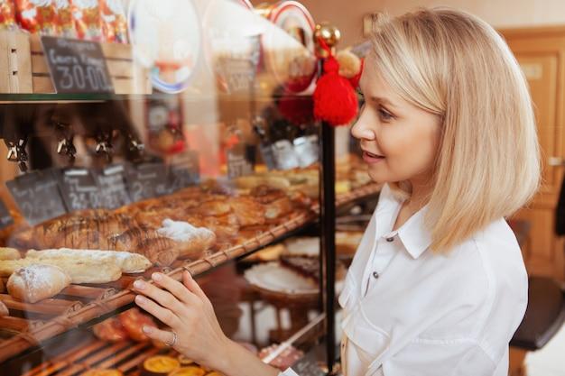 Jonge vrouw heerlijke desserts op het display in de coffeeshop te onderzoeken