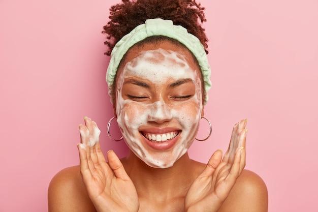 Jonge vrouw heft de handpalmen op het gezicht, houdt de ogen gesloten, toont witte tanden, gebruikt reinigingsschuim voor huidverzorging, krijgt echt plezier