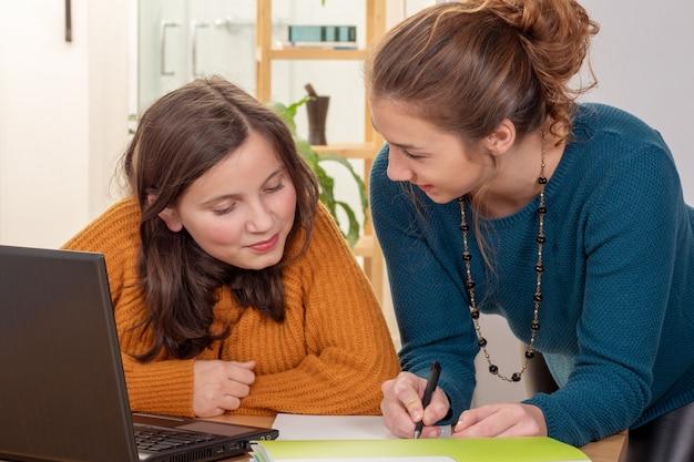 Jonge vrouw helpt een tienermeisje met huiswerk