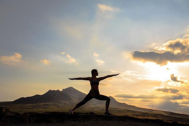 Jonge vrouw het beoefenen van yoga bij zonsondergang op prachtige berglocatie.