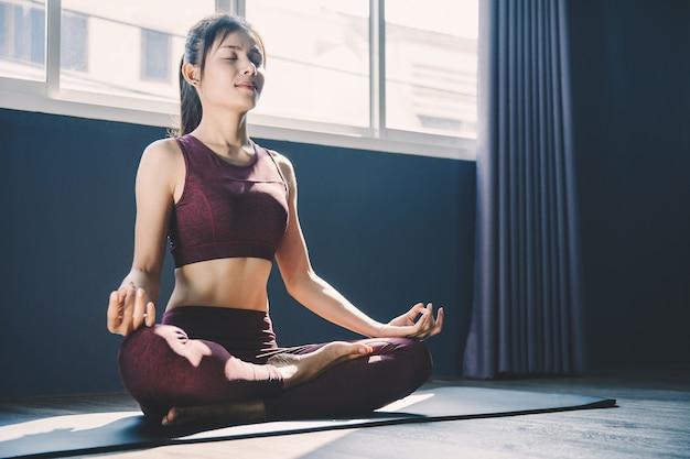 Jonge vrouw het beoefenen van yoga in de klas; mooi meisje gevoel kalmte en ontspannen in yogales