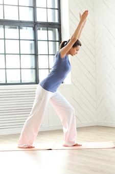 Jonge vrouw het beoefenen van yoga op een yogamat