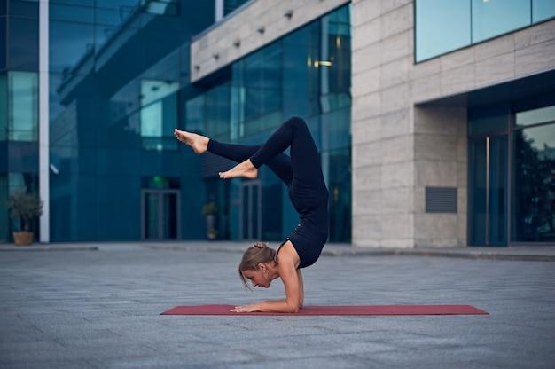 Jonge vrouw het beoefenen van yoga, staande in vrischikasana scorpion pose buitenshuis