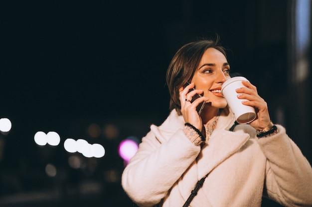 Jonge vrouw het drinken koffie bij nachtstraat